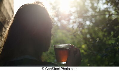 Woman having tea outdoor during sunset