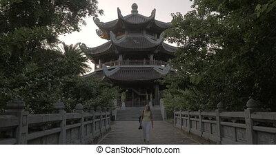 Woman having touristic walk in Bai Dinh Temple area, Vietnam