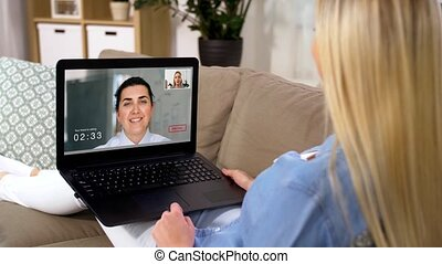 woman having video call on laptop computer at home -...