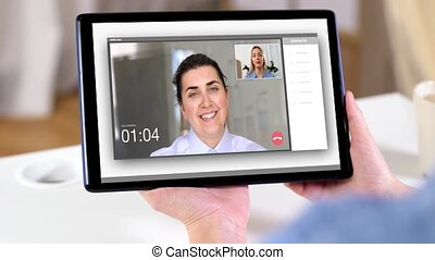 woman having video call on tablet computer at home -...