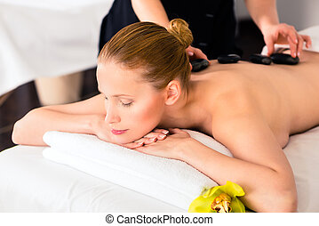 Woman having wellness spa hot stone massage