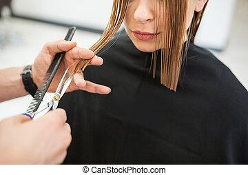 Woman having wet hair cut at hairdresser