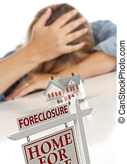 Woman, Head in Hand Behind Model Home and Foreclosure Sign -...