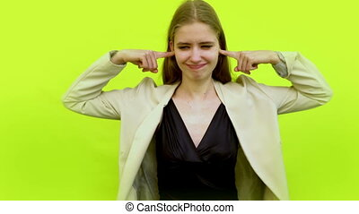 Woman having headache covering ears with fingers and ignoring annoying conversation in space studio on background color yellow. Irritated businesswom don't want to listen. Noise problem concept.
