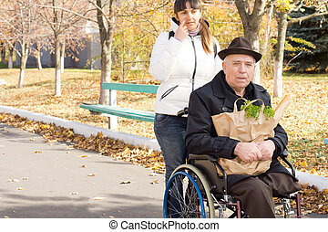 Woman helping an elderly disabled man