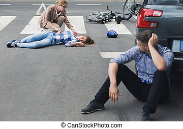 Woman helping an unconscious victim while shocked driver...
