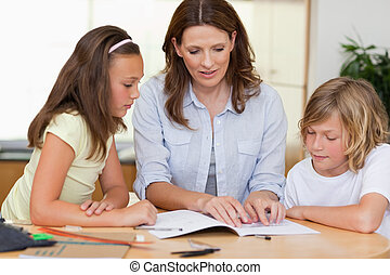Woman helping children with homework - Woman helping her...