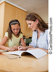Woman helping daughter with homework - Woman helping her...
