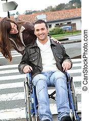 Woman helping friend in wheelchair cross the street