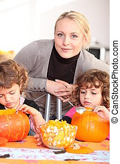 Woman helping her children carve pumpkins