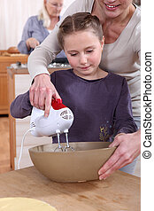 Woman helping her daughter use a hand mixer