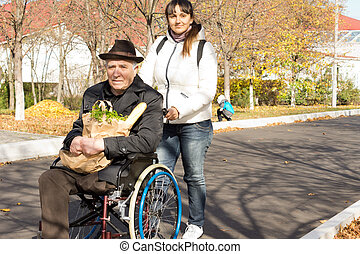 Woman helping her senior handicapped father pushing him...
