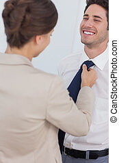 Woman helping her smiling husband to tie his tie