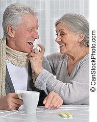 woman helping husband to use inhaler