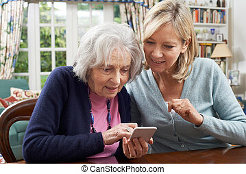 Woman Helping Semior Neighbor To Use Mobile Phone