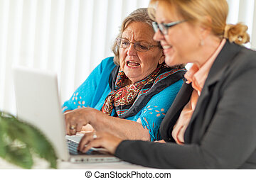 Woman Helping Senior Adult Lady on Laptop Computer