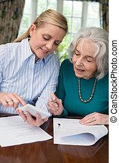 Woman Helping Senior Neighbor With Paperwork