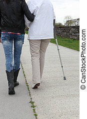 woman helping senior to walk