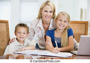 Woman helping two young children with laptop do homework in dini
