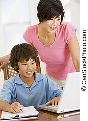 Woman helping young boy with laptop do homework in dining room s
