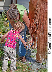 Woman Helps Toddler Clean Horse Shoe