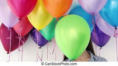 Woman hides her head an air colorful balloons