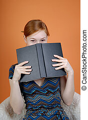 Woman hides the face behind the book
