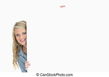 Woman hiding behind a poster