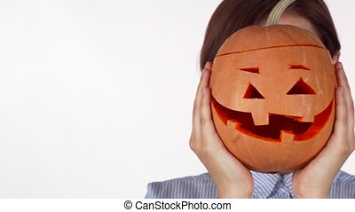 Woman hiding behind carved Halloween pumpkin isolated