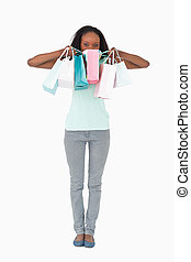 Woman hiding behind her shopping on white background