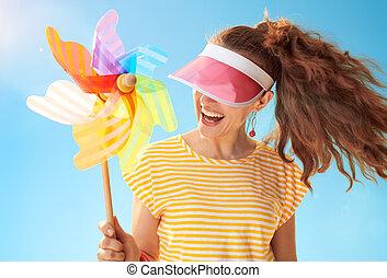 woman hiding behind sun visor holding colorful windmill - ...