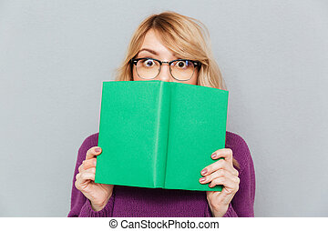 Woman hiding face with book