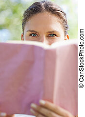 Woman hiding her face behind a book in the park