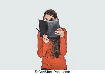 Woman hiding her face behind a notebook.