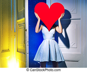 Woman hiding herself behind a heart - Lady hiding herself...