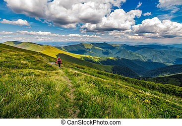 woman hike through grassy slope in mountains - woman in red...