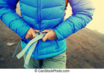 woman hiker buckle up the belt of backpack