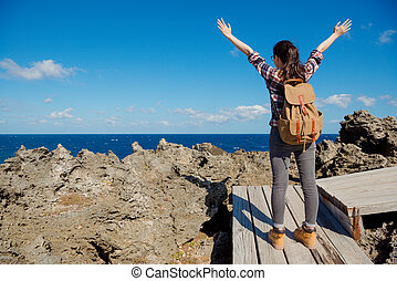 woman hiker cheering success and joy in front of sea and sky...