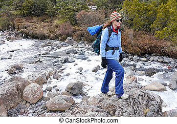 Woman hiker crossing a frozen stream