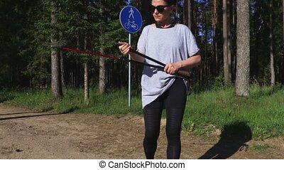 Woman hiker fixing Nordic walking poles near trail