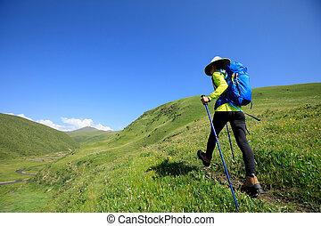 woman hiker hiking on grassland trail