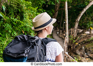 woman hiker in hike with a big backpack back view