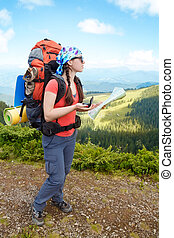 Woman hiker in mountains determines the direction
