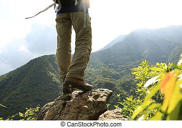 woman hiker legs climbing on mountain peak rock