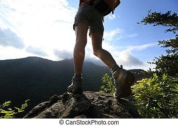 woman hiker legs climbing on sunrise mountain peak rock