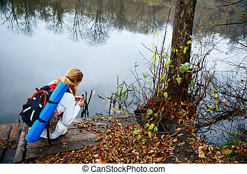 Woman hiker on a wooden platform in the autumn river