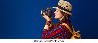 woman hiker on blue background taking photo with digital camera