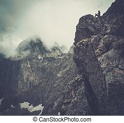 Woman hiker sitting on a mountain peak