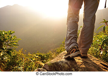 woman hiker stand on mountain peak rock