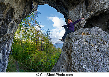 Woman hiker standing on the cliff in a doline